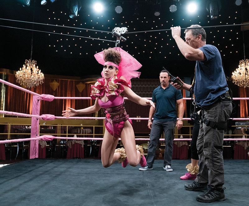 Trabajando sin red. La actriz Alison Brie se prepara para realizar una acrobacia en el set de la serie que protagoniza, GLOW. Los altos gastos de Netflix en contenido original la ponen en riesgo de pérdidas si no mantiene el interés de las audiencias. | Foto: Cortesía Netflix