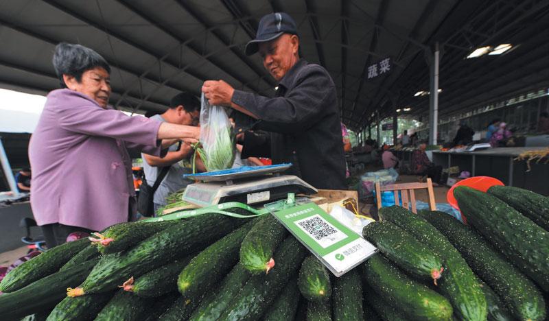 En Weifang, China, un código QR posibilita que un comerciante de verduras cobre su producto por medio de un smartphone, sin intervención del efectivo. | Foto: Getty Images