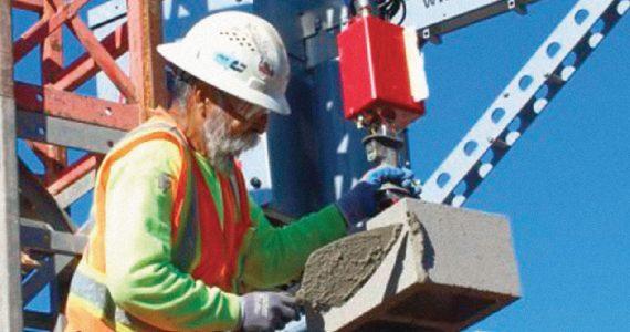 El robot MULE, de Construction Robotics, levanta bloques pesados de concreto,mientras un trabajador los coloca adecuadamente. | Foto: Cortesía de Clark Construction