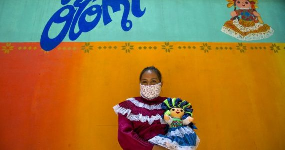 Familias de Santiago Mexquititlán viven en un edificio frente al que han montado un bazar. | Foto: AFP